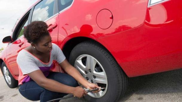 woman fixing car wheel