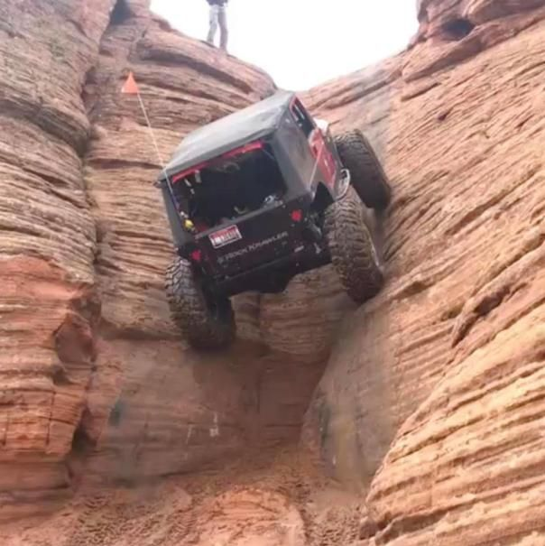 A Jeep climbing up a huge rock at a 90-degree angle