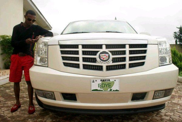 "Francis Agoda stands by his car with the pricey personalized number plate ""IgoDYE"""