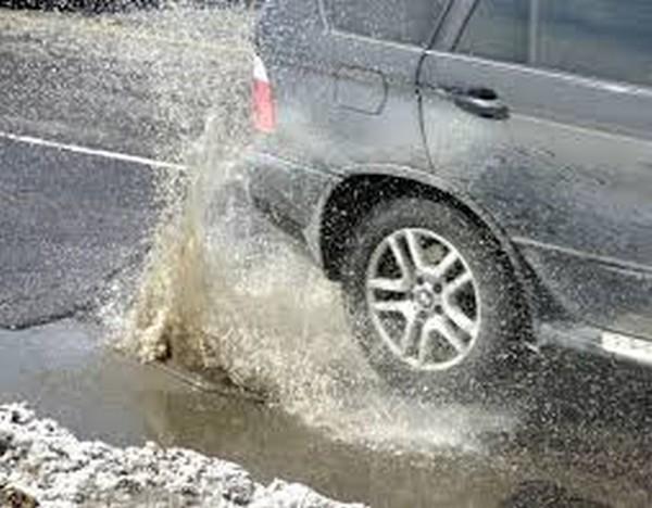 A Car encountering a pothole
