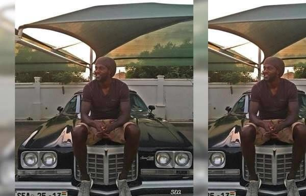 Emmanuel Adebayor sits in front of his car