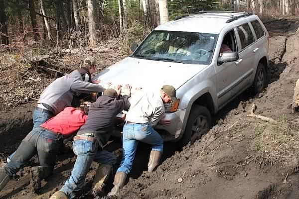 People push a car out of a swamp