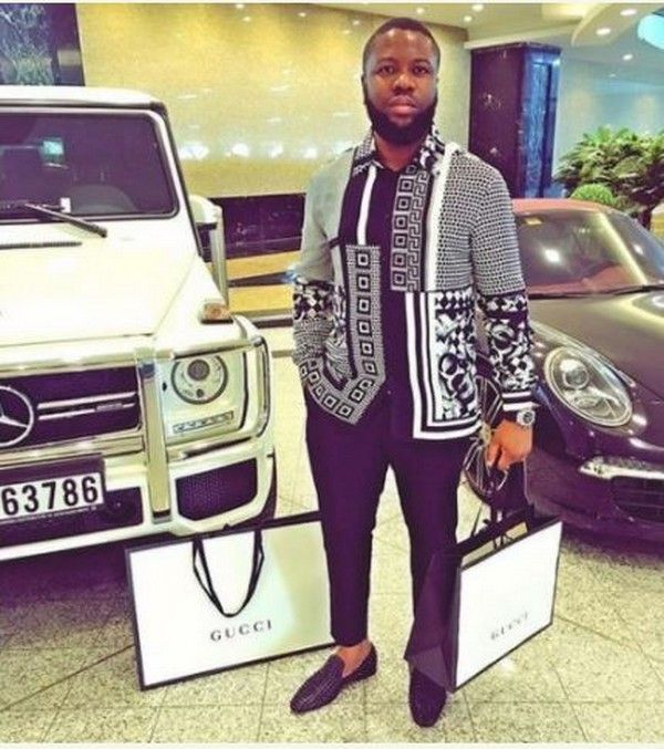 Hushpuppi is carrying a Gucci bag next to two extremely costly cars