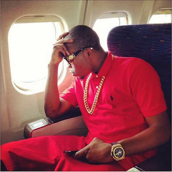 Olamide posing near a private jet's window