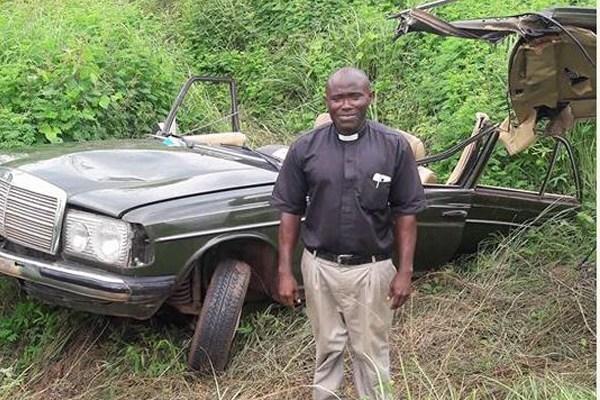 Okey Okibe poses beside his damaged car