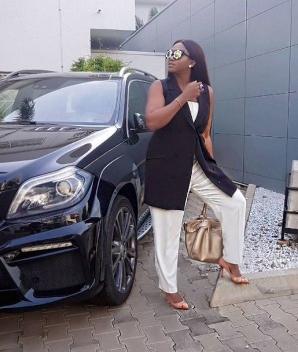Waje posing along her car