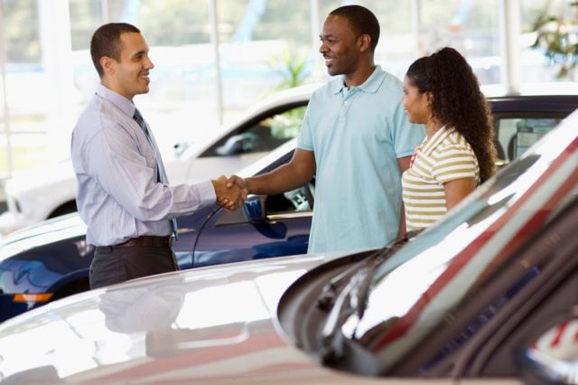 a couple of buyers shaking hands with a car seller
