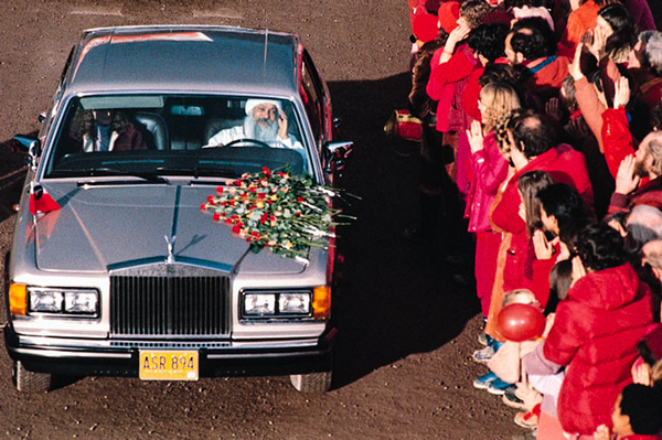 Osho Rajneesh in his Rolls-Royce passing by his followers