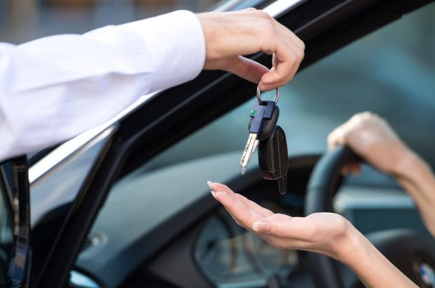 someone handding over a car key to someone else