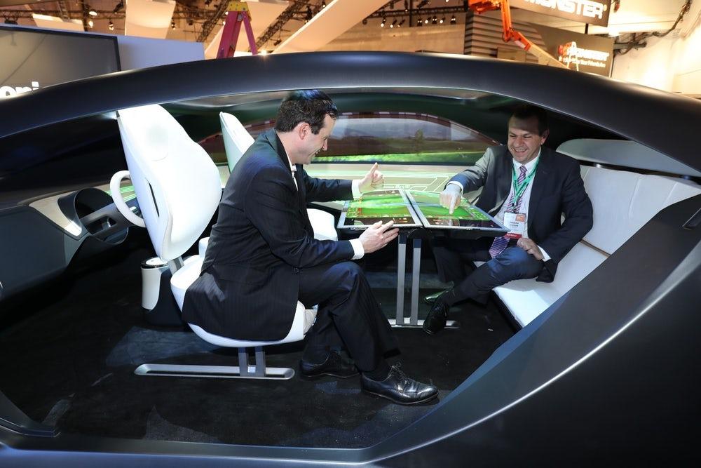 two men discussing in an autonomous car