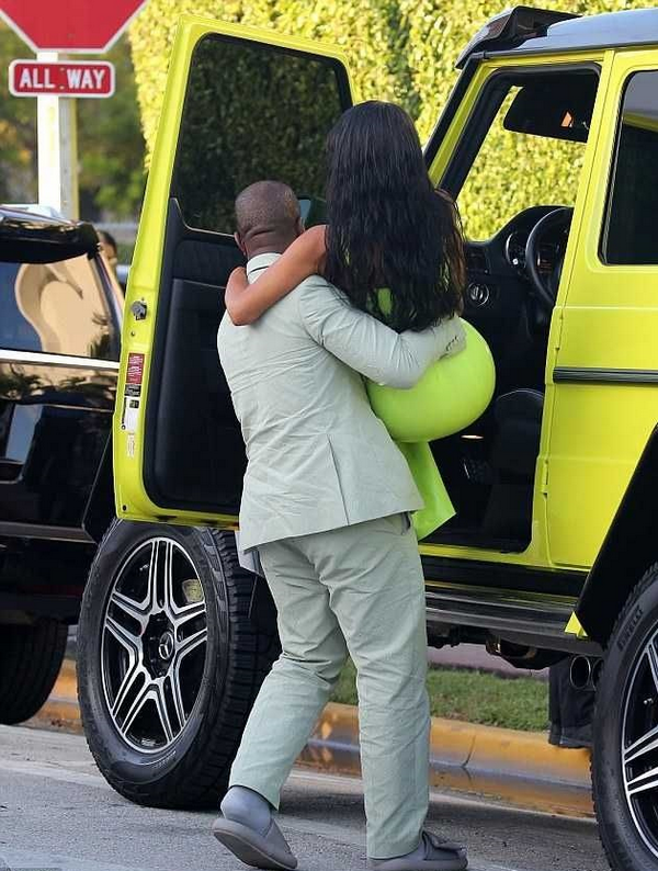 Kayne carries his wife into the Mercedes-Benz