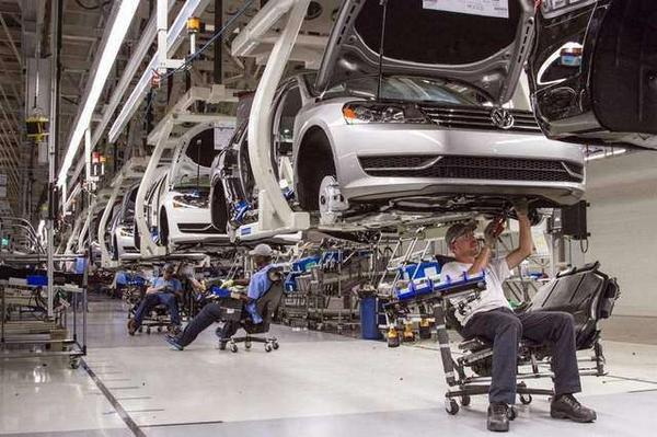mechanics assembling Volkswagen vehicles in a plant