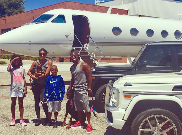 Kevin Hart and his family beside his private jet
