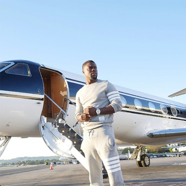 Kevin Hart posing for a picture with his private jet
