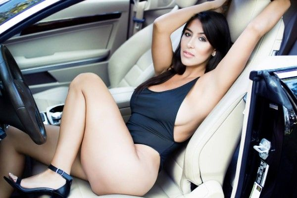 a sexy girl lying on the driver seat of a Mercedes Benz E350