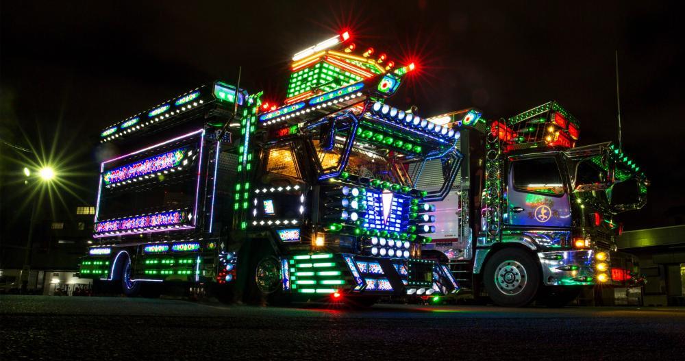 two dekotora trucks with illuminating lights