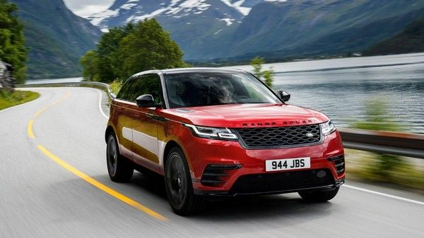 a red Range Rover Velar running on a lake-side path
