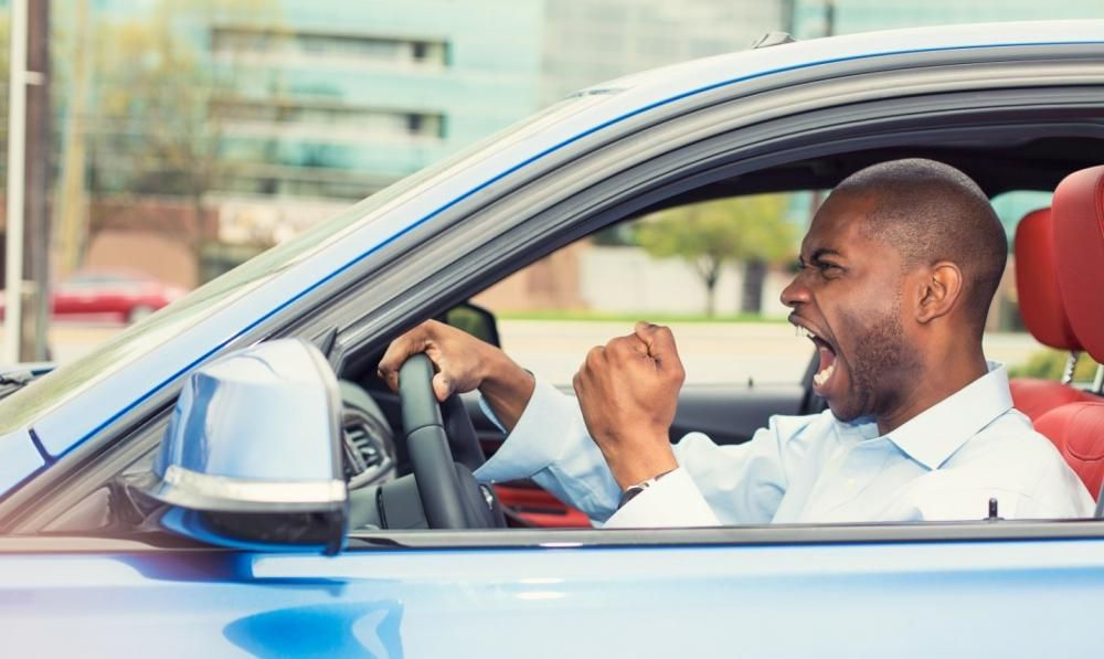 a black man in car cursing at something