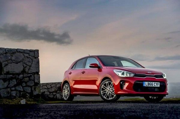 a red Kia Rio and sky background