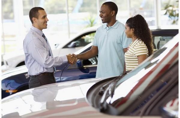 a car salesman and 2 customers