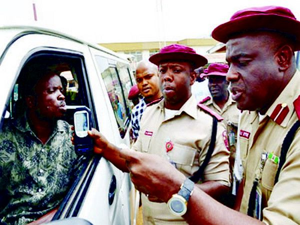 Nigerian marshal checking a car driver
