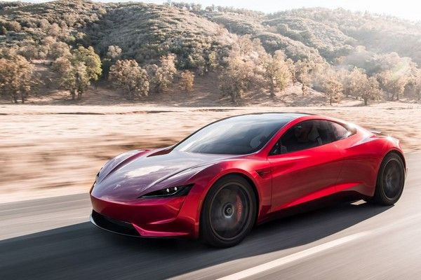 a red Tesla Roadster on the road