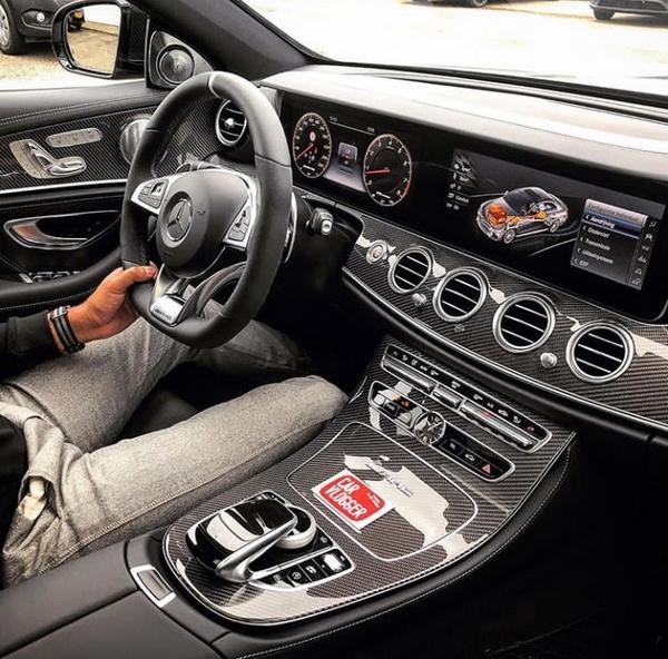 A man driving a black Mercedes-Benz