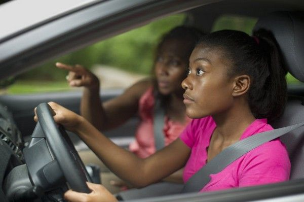 a girl learning to drive with instructor