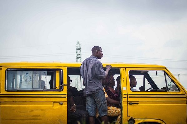 bus conductor hanging out of a Danfo