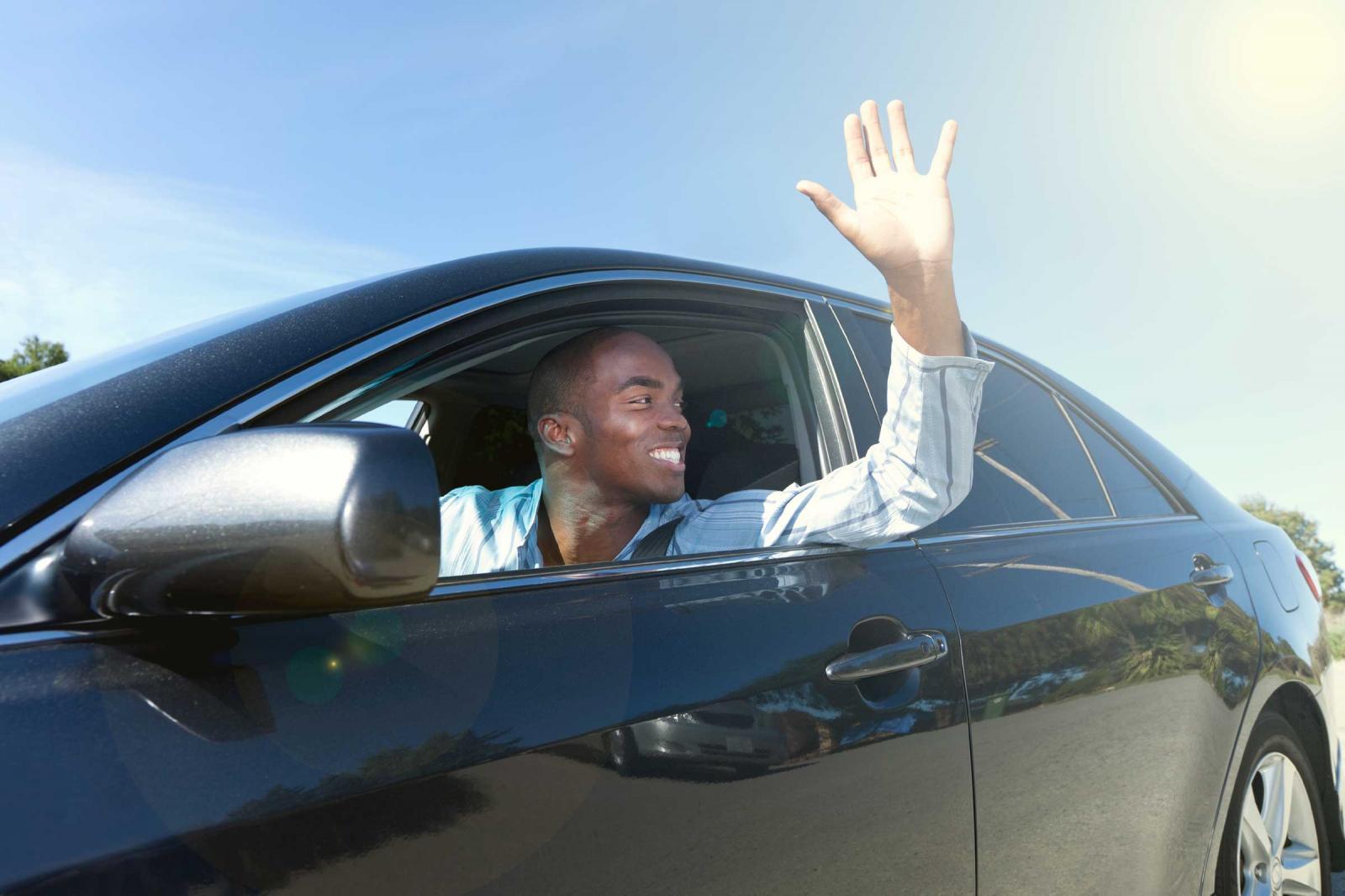 a black man inside a car with a window down