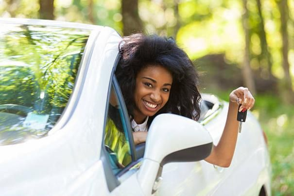 a happy black woman in a car