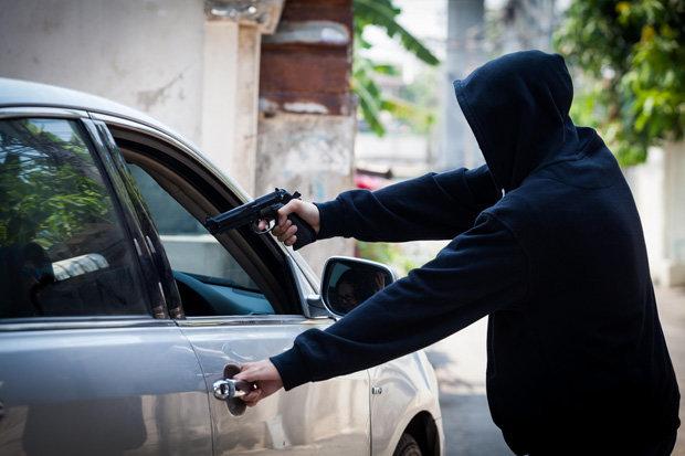 an armed man point a gun at a car