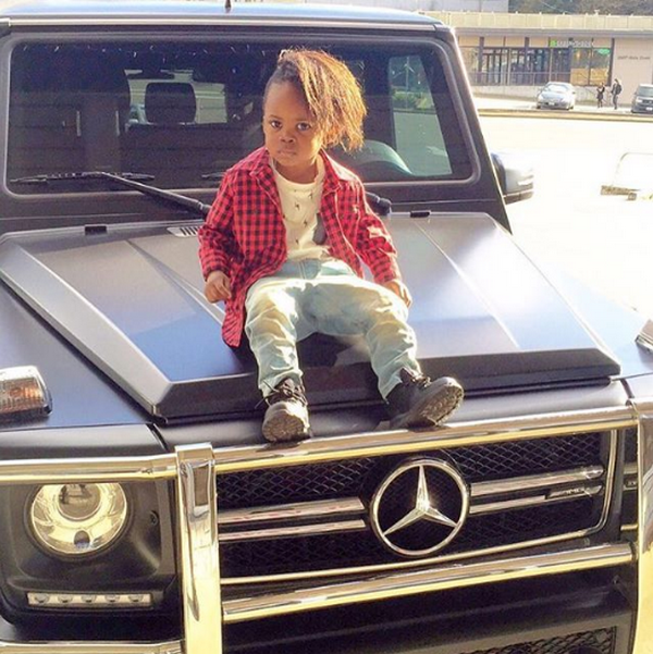 Obafemi-Martins'-son-sitting-on-the-hood-of-his-Mercedes-Benz-G-Class
