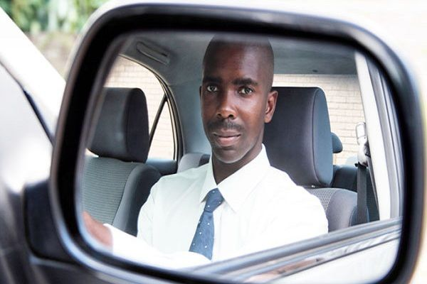 Black-man-looks-at-a-side-mirror