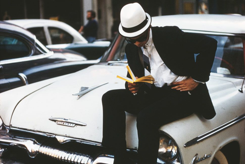 a-man-on-a-car-reading-the-manual