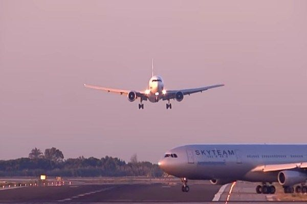 a-plane-taxying-across-runway-of-another-plane