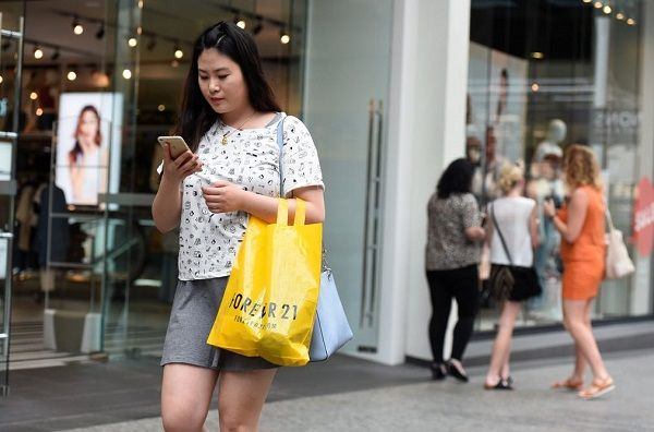 image-of-a-lady-pressing-phone-while-walking