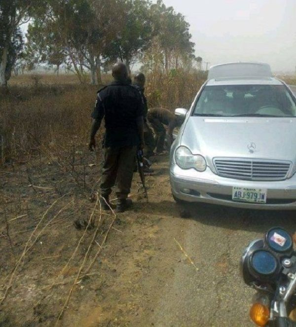 Nigerian-Police-officers-gather-to-help-man-change-tires