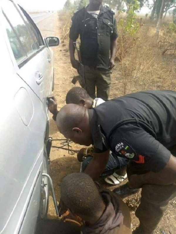 Nigerian-Police-officer-help-civilian-to-remove-bad-tire