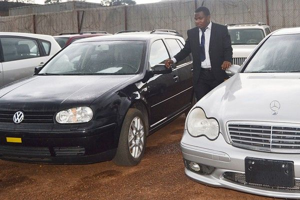 a-black-man-is-standing-between-two-cars