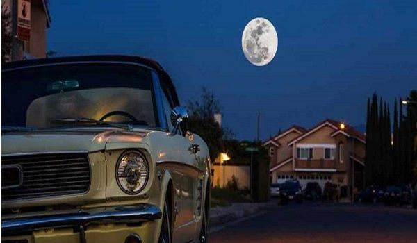 Car-parked-outside-at-night-with-full-moon