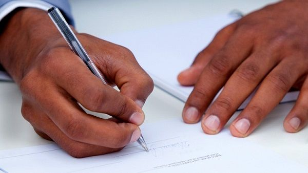 A-black-hand-signing-a-document
