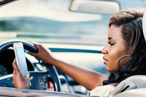 woman-in-car-looks-at-phone