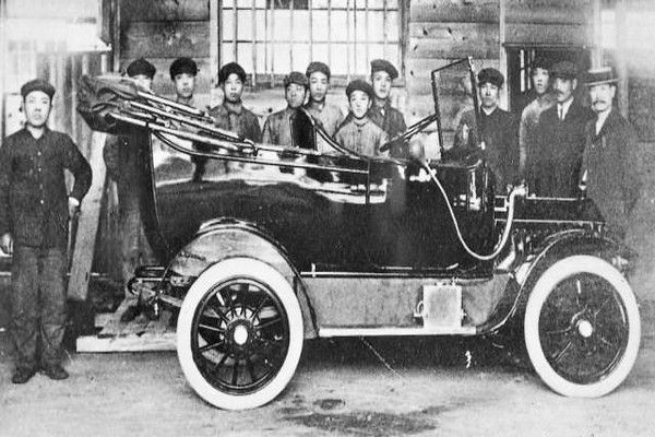 men-gathered-around-car-to-take-a-picture
