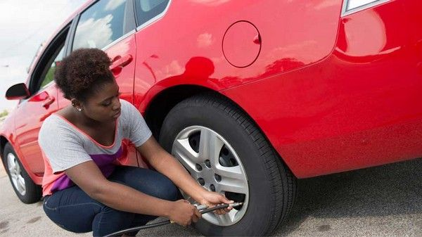 Black-woman-changing-car-tire