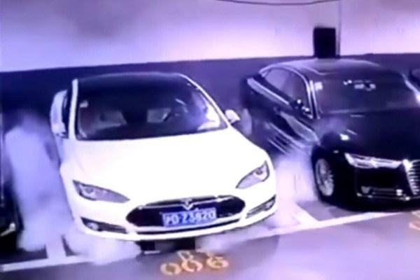 Parked-white-Tesla-Model-S-car-emitting-smoke