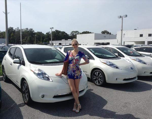 lady-standing-with-a-Nissan-leaf