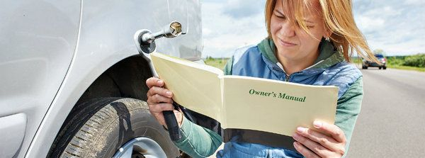 A-lady-using-a-hard-copy-manual-for-DIY-repair