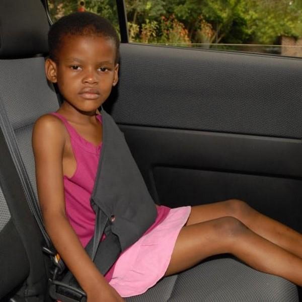 Little-black-girl-seated-in-car-rear-seat
