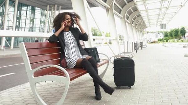 Woman-makes-a-call,-seated-on-airport-bench
